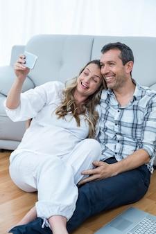 Enceinte couple assis sur le sol à l'aide de téléphone portable dans le salon