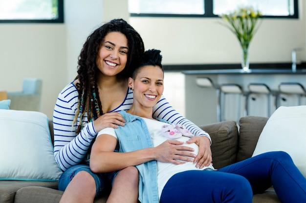 Enceinte couple de lesbiennes assis sur le canapé avec une paire de chaussures de bébé rose