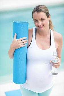 Enceinte femme tenant une bouteille d'eau et un tapis à côté de la piscine