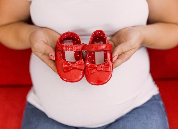 Enceinte femme tenant des chaussures rouges