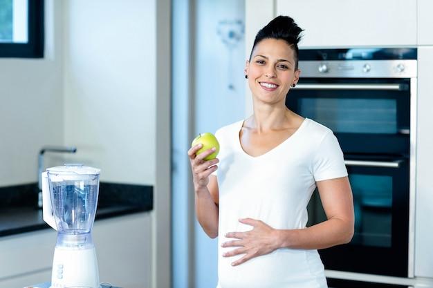 Enceinte femme tenant une pomme verte et souriant dans la cuisine