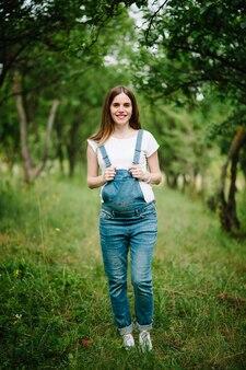 Enceinte fille heureuse se tenir debout et tenir les mains sur le ventre dans le fond de jardin avec des arbres.