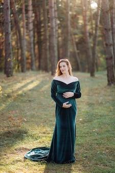 Enceinte heureuse jeune femme marchant à l'extérieur dans la forêt
