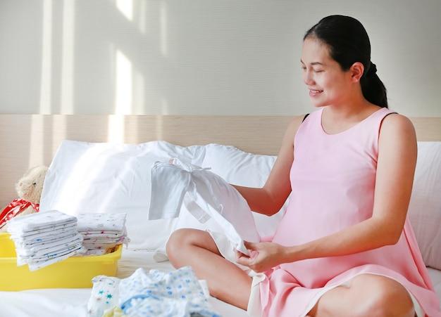 Enceinte mère asiatique emballant des vêtements de bébé pour aller à l'hôpital dans quelques jours
