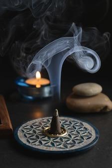 Encens aromatique à côté d'une bougie allumée