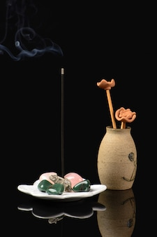 Encens avec éléphant et pierres et vase en céramique sur fond noir