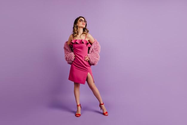 Enchanteur dame en tenue rose debout dans une pose confiante