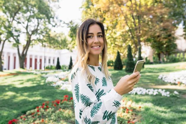 Enchanteur femme bronzée regarde à l'avant avec un sourire inspiré tout en marchant dans le parc