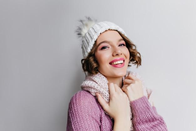 Enchanteur fille bouclée avec une expression de visage heureux posant dans un pull violet et des accessoires blancs. photo intérieure d'un beau modèle féminin caucasien porte un bonnet et une écharpe tricotés.
