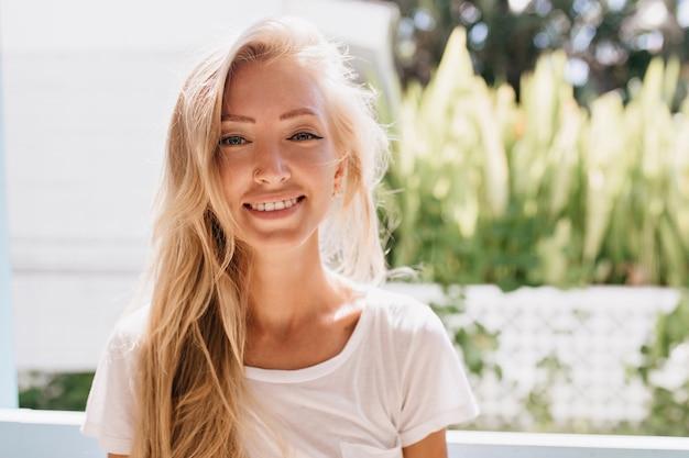 Enchanteur jeune femme porte des vêtements blancs posant. joli modèle féminin bronzé souriant à cause de la bonne humeur.