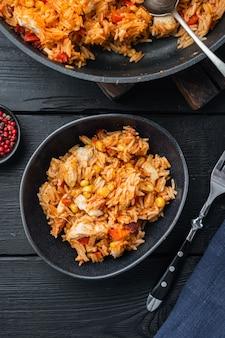 Enchiladas mexicaines traditionnelles avec de la viande de poulet, du riz et du fromage cuisine mexicaine., sur fond de table en bois noir, vue de dessus à plat