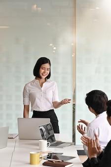 Encouragement d'un collègue devant une jeune femme d'affaires expliquant son idée dans la salle de réunion.