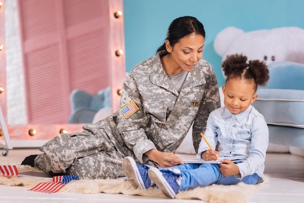 Encourager l'éducation. charmante femme bienveillante charismatique aidant sa fille à composer une belle pièce pour un cours d'écriture tout en passant son temps libre avec elle et assise confortablement sur le sol
