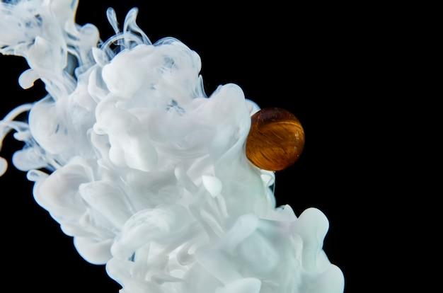De l'encre acrylique blanche dans l'eau sur fond noir entoure la boule de verre. abstrait.
