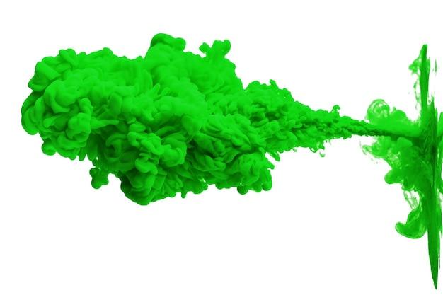 L'encre acrylique dans l'eau forme un motif de fumée abstraite isolé sur un mur blanc