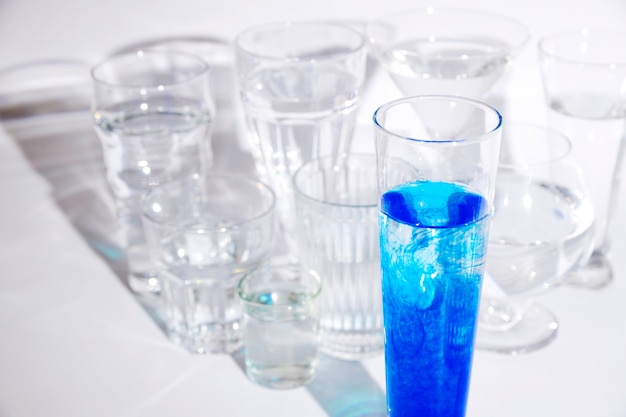 Encre cyan dissoute dans l'eau à l'intérieur du verre