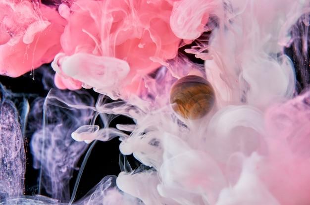 Des encres acryliques roses et blanches dans l'eau sur fond noir entourent la boule de verre. abstrait.