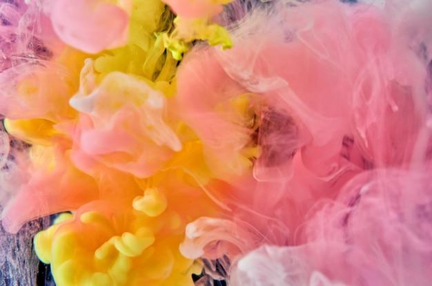 Des encres acryliques roses, blanches et jaunes dans l'eau sur fond noir entourent la boule de verre. abstrait.