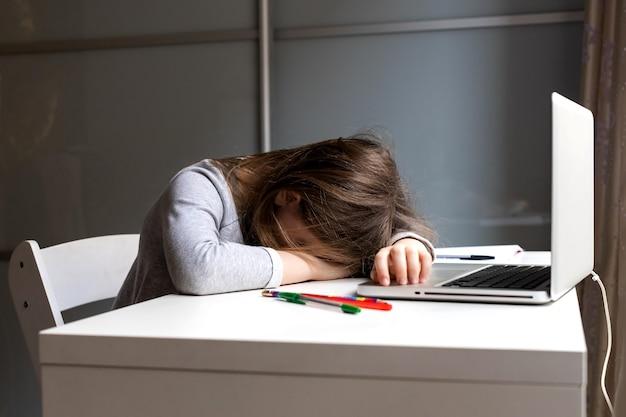 Endormi assis au bureau à la fille de l'ordinateur portable
