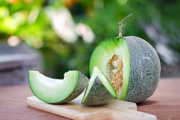 Endroit tranché de melon frais sur une planche à découper en bois sur une table en bois