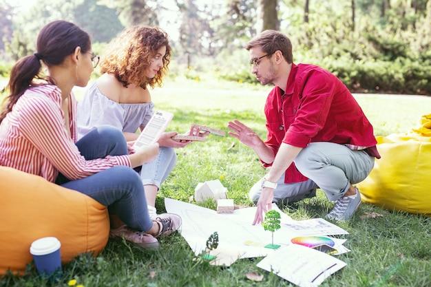 Endroit de travail. beau jeune homme parlant avec ses collègues tout en travaillant en plein air