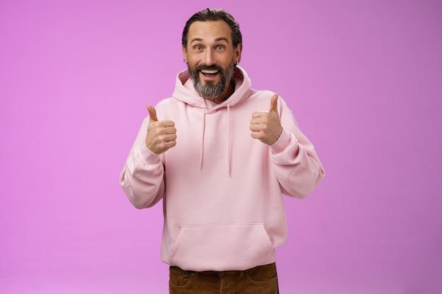 Énergisé de soutien heureux charmant hipster homme mûr barbu cheveux gris montrer les pouces vers le haut geste oui signe d'approbation totalement d'accord applaudir la racine pour un ami comme une idée géniale, debout fond violet.