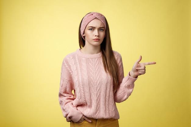 Énervé, perplexe, jeune copine de mauvaise humeur arrogante et séduisante dans un bandeau de chandail à la recherche d'une inte irritée...