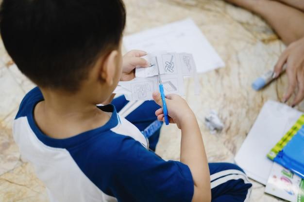 L'enfance apprend à utiliser des ciseaux pour couper du papier.