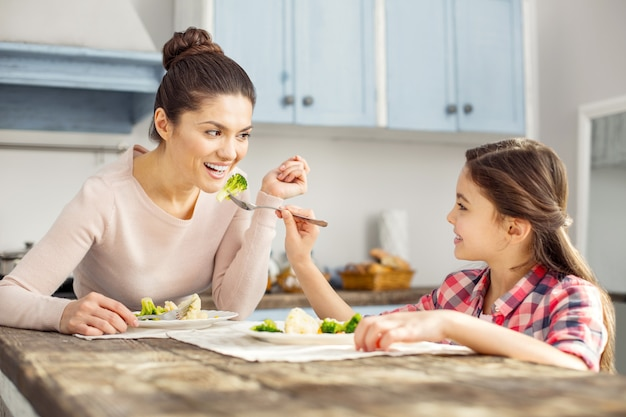 Enfance heureuse. belle jeune mère aux cheveux noirs alerte souriant et manger des aliments sains avec sa fille et sa fille la nourrissant