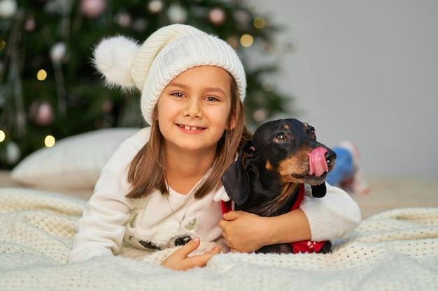 Enfance heureuse, conte de fées magique de noël. une petite fille rit avec son ami, un chien teckel, près du sapin de noël.