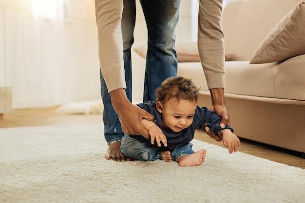 Enfance. heureux petit garçon aux yeux sombres assis sur le sol et jouant pendant que son papa afro-américain tenant ses mains