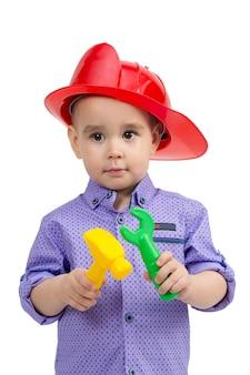 Enfant de 3 ans dans un casque avec des outils de construction en mains.