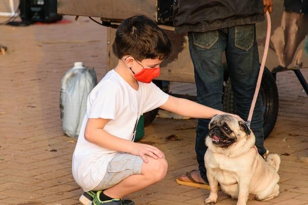 Enfant de 8 ans, avec masque, accroupi et caressant un chien carlin.