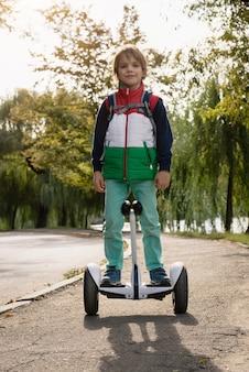 Enfant actif à cheval sur hoverboard électronique blanc moderne dans un parc de la ville à l'automne soigné le lac