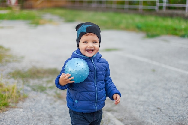 Enfant actif dans une veste avec un ballon dans les mains