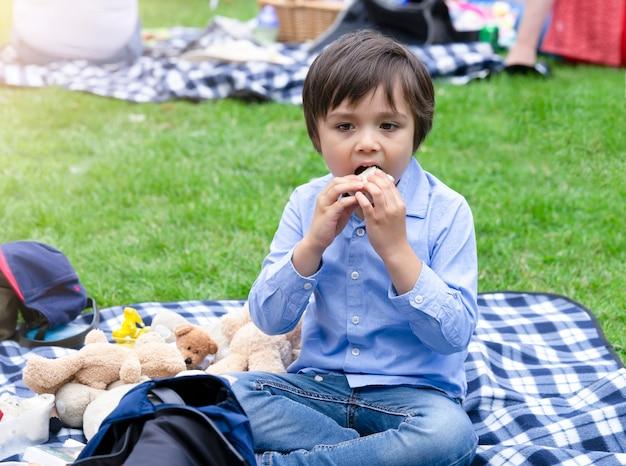Enfant affamé mangeant des tortillas fraîches avec un mélange de légumes au saumon