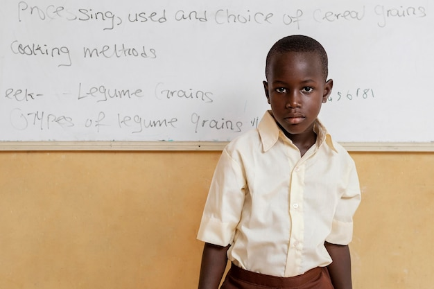 Enfant africain debout à côté d'un tableau blanc