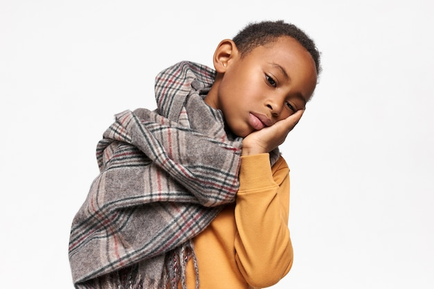 Enfant africain malade bouleversé ayant le rhume ou la grippe étant malade, posant isolé dans un foulard chaud, tenant la main sous la joue