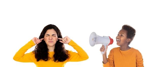 Enfant africain avec un mégaphone et une adolescente couvrant ses oreilles isolé sur un blanc