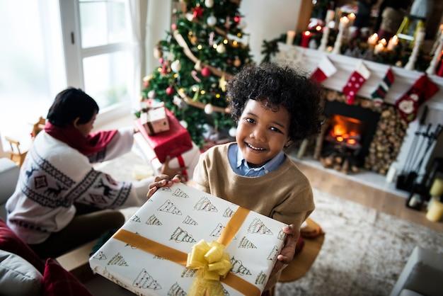 Enfant africain tenant un cadeau de noël