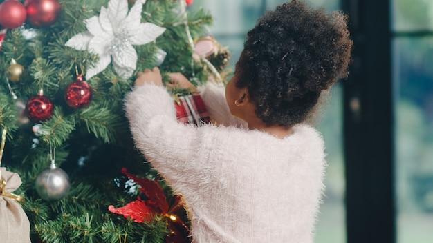 Enfant afro-américain décoré d'ornement sur l'arbre de noël