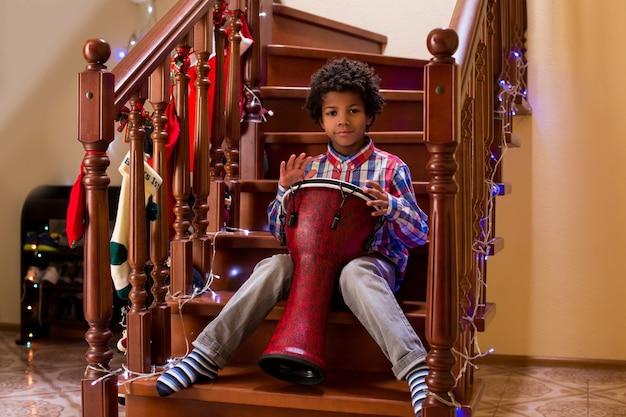 Un enfant afro joue du tambour kid avec du tambour à noël, un jeune talent de percussionniste l'appelle son premier concert