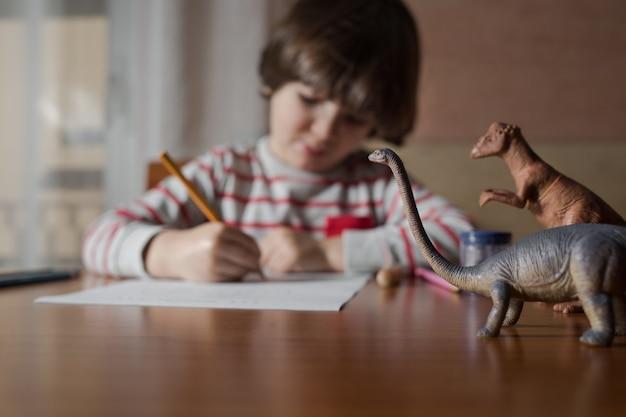 Enfant d'âge préscolaire, dessin sur la table dans sa maison
