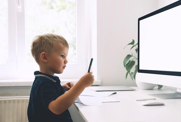 Enfant d'âge préscolaire utilisant la technologie informatique pour le développement précoce ou le divertissement à la maison