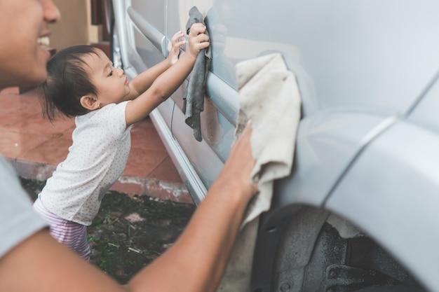 Enfant aidant son papa à nettoyer la voiture
