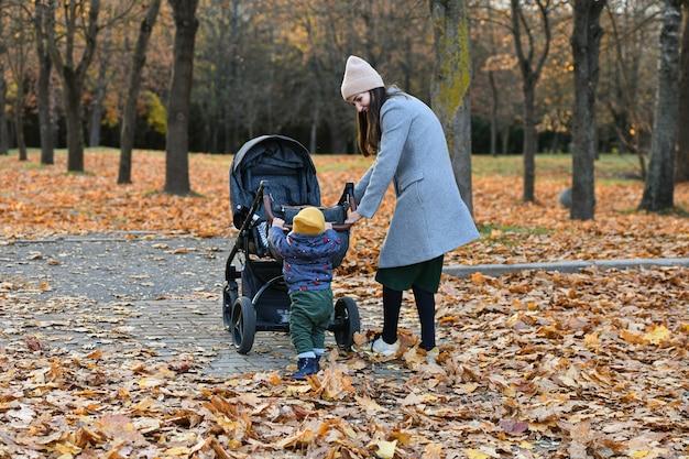L'enfant aide maman à pousser la poussette.