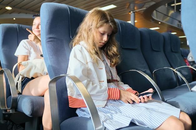 Enfant à l'aide de smartphone assis à l'intérieur du ferry