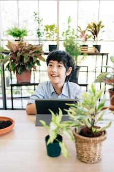Enfant à l'aide de tablette étudiant la plantation pendant sa leçon en ligne à la maison