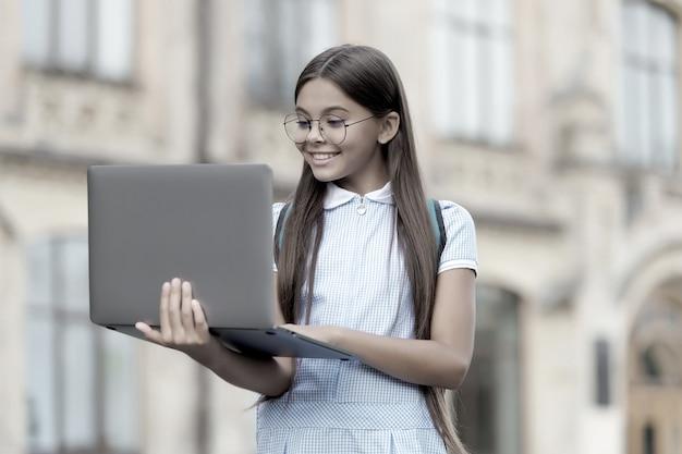 Enfant à l'air intelligent dans les gaz tapant sur un ordinateur à la recherche d'informations sur internet pour l'éducation scolaire en ligne, le développement de l'enfance.
