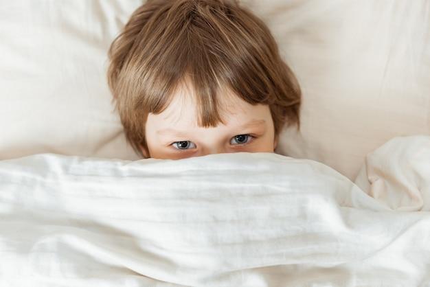 Enfant allongé sur le lit, heure du coucher heureuse dans la chambre blanche